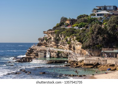 Sydney, Australia - February 11, 2019: Focus on the South Cliff at Bronte Beach with swimming pool in front. Peple in water and on sand. Housing in green vegetation on top of rocks.
