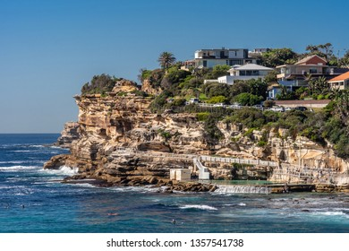Sydney, Australia - February 11, 2019: Focus on the South Cliff at Bronte Beach with swimming pool in front. Peple in water. Housing in green vegetation on top of rocks.