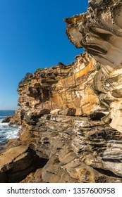 Sydney, Australia - February 11, 2019: Spectacular rock outcrop at Bronte Beach South cliffs, made by erosion.. Yellows and browns under blue sky. Sponge-like borders of shell like plates.