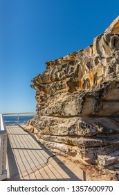 Sydney, Australia - February 11, 2019: Path ends at spectacular rock outcrop at Bronte Beach South cliffs, made by erosion.. Yellows and browns under blue sky. Sponge-like borders of shell like plates