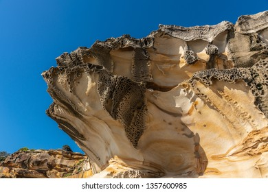 Sydney, Australia - February 11, 2019: Closeup of spectacular rock outcrop at Bronte Beach South cliffs, made by erosion.. Yellows and browns under blue sky. Sponge-like borders of shell like plates