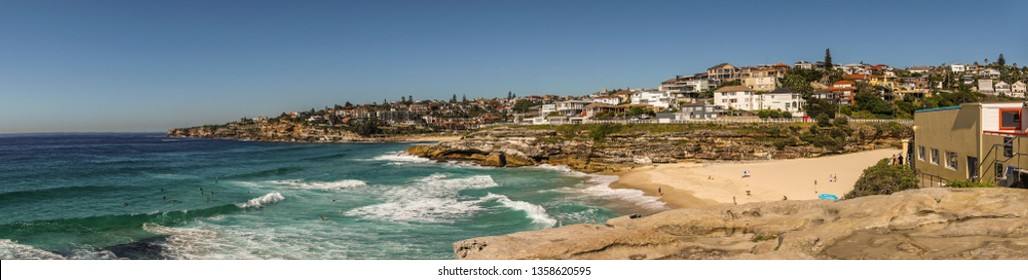 Sydney, Australia - February 11, 2019: Panorama shot of sandy Tamarama beach in front and Bronte Beach in distance. Rochy shorelines and plenty of housing. Blue sky and sea.