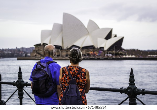 Sydney, Australia - FEBRUARY 14, 2017: The Sydney Opera House is a multi-venue performing arts centre identified as one of the 20th century's most distinctive buildings.Couple watching opera house