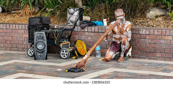 Sydney, Australia - February 24th 2019: Aboriginal men playing the didgeridoo. Street performance in Australia.