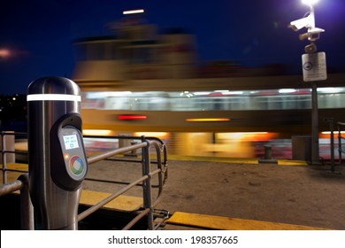 SYDNEY, AUSTRALIA - FEBRUARY 6,2014: An Opal Card reader awaits passengers from an approaching ferry. The tap-on / tap-off payment system is being rolled out to all Sydney buses, trains and ferries.