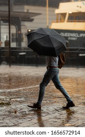 Sydney, Australia, February 9 2020, A man walking with umbrella during strong wind at Circular Quay