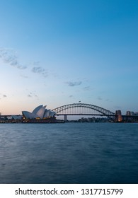 Sydney, Australia - January 16, 2019: Sydney Opera House and Harbour Bridge at dusk with clear sky.