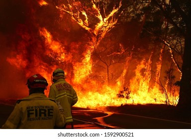 SYDNEY, AUSTRALIA - January 21, 2020: Fire and Rescue personal run to move their truck as a bushfire burns next to a major road and homes on the outskirts of the town of Bilpin on December 19, 2019