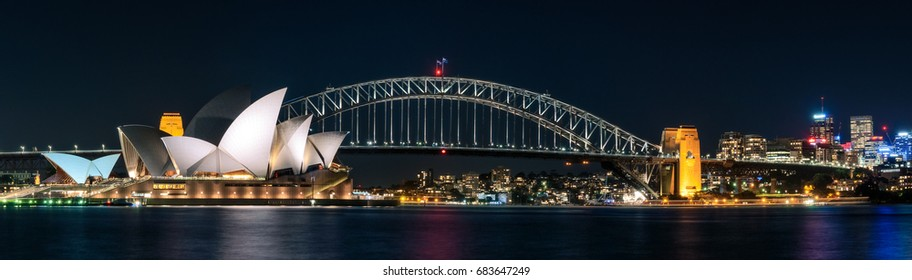 Sydney, Australia -July 18, 2017: Panorama postcard view of Sydney Harbour with the two famous icons Opera House and the Harbour Bridge in long exposure photography.