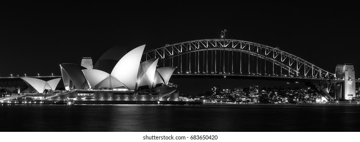 Sydney, Australia -July 18, 2017: Panoramic view in black and white of Sydney Harbour with the two famous icons Opera House and the Harbour Bridge in long exposure photography.