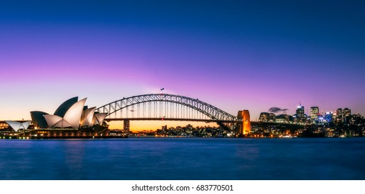 Sydney, Australia -July 18, 2017: Sunset over Opera House and the Harbour Bridge in Sydney, Australia. Panoramic View from Lady Macquarie's Chair.