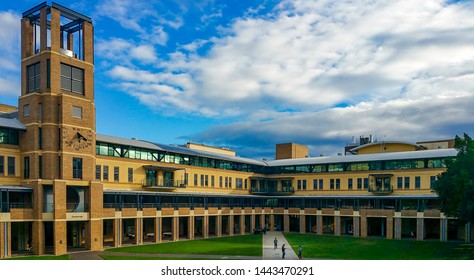 Sydney, Australia - Jun 20, 2016: Dramatic white clouds and blue sky hovering over the Quadrangle Building of the University of New South Wales, Kingsford Campus. A few people in the foreground.
