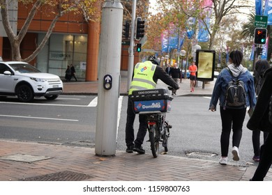 Sydney, Australia - June 1 2018:  Dominos Pizza bike delivery and pedestrians are crossing a street in Sydney.