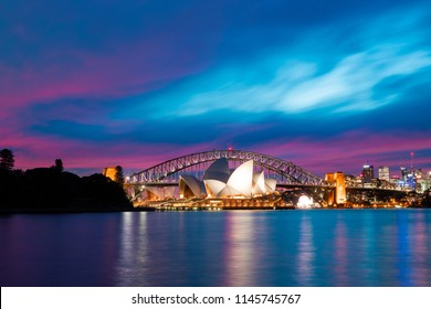 Sydney, Australia - June 29, 2018: Dusk view of Sydney Opera House in front of Sydney Harbour Bridge.
