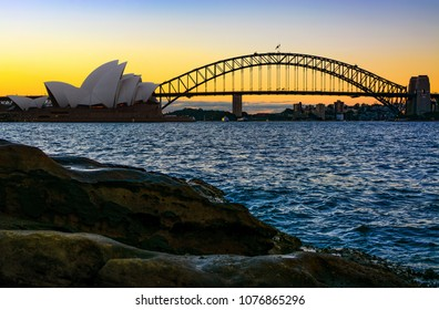 SYDNEY, AUSTRALIA - MARCH 10, 2018 - Sydney Opera House and Harbour Bridge, the city's iconic landmarks, seen from natural shoreline at sunset