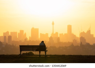 Sydney, Australia - March 12, 2019: A man sitting down at the bench in the park with Sydney skyline on the background.