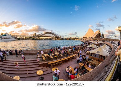 Sydney, Australia - March 2017: Tourists and locals enjoy drinks and happy hour at sunset on a warm summer evening near the Opera House. in the Background the Harbour Bridge