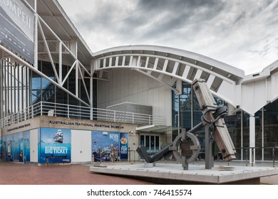 Sydney, Australia - March 21, 2017: Main entrance white facade to National Maritime Museum under heavy cloudscape. Huge Anchor statue in front. Blue advertisement posters.