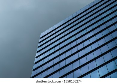 Sydney, Australia - March 22, 2019: Minimalist glass facade of a tall building with cloudy dark sky.