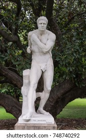 Sydney, Australia - March 23, 2017: Half of historic white marble statue duo called The Boxers, by 19th century Italian Antonio Canova in Botanical Garden. Dark green background.