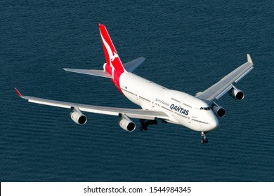Sydney / Australia - March 25 2018: Aerial view of Qantas Airways Boeing 747 in final approach to Sydney Airport over Botany Bay waters. Air to air image of four engines jet before landing.