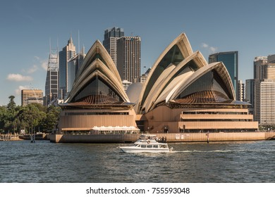 Sydney, Australia - March 26, 2017: Frontal view of Opera House seen off the water with office towers in back and small boat in front under blue sky.