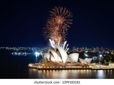Sydney, Australia - March 8, 2018 - Showers of gold fireworks erupting over the beloved Sydney Opera House at night