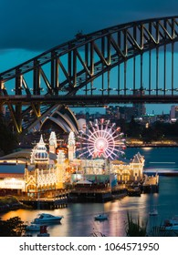 SYDNEY, AUSTRALIA - MARCH 9, 2018: Night view of Luna Park, Sydney Harbour Bridge, and the iconic Opera House.
