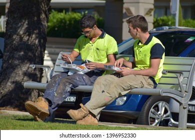 Sydney / Australia - May 11 2019: View of two tradies in bright yellow t-shits having breakfast on bench at Manly Beach