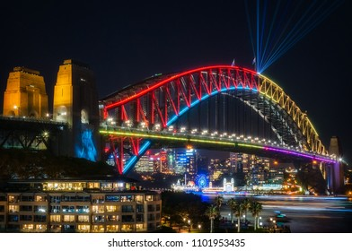 Sydney, Australia -May 25, 2018: Vivid Sydney Festival in Sydney Harbour, Australia. Close up to Sydney Harbour Bridge dressed up in multiple colors and with laser beams shot from the top of the arch.