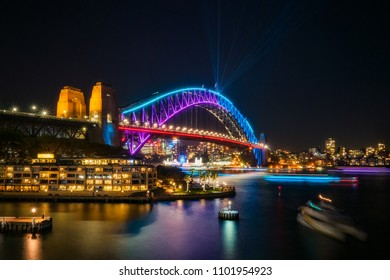 Sydney, Australia -May 25, 2018: Vivid Festival in Sydney Harbour, Australia. View of Sydney Harbour Bridge illuminated for the Vivid Show and with North Sydney Skyline and Luna Park in the background
