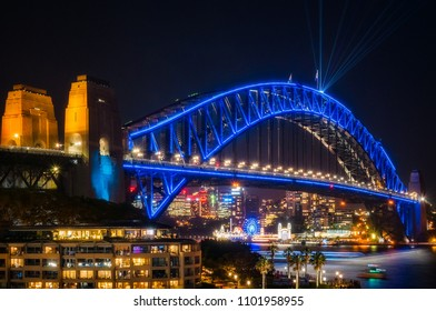 Sydney, Australia -May 25, 2018: Vivid Festival in Sydney Harbour, Australia. Close up to Sydney Harbour Bridge illuminated in blue and with laser beams shot from the top of the arch.