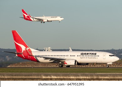 Sydney, Australia - May 5, 2014: Qantas Boeing 737 at Sydney Airport with another Qantas 737 landing in the background.