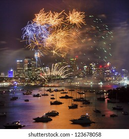 sydney australia new year firework over city cbd and harbour with reflection of lights in water with yachts and illumination
