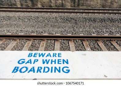 Sydney, Australia - Nov 14, 2017: Gap warning sign stencil printed between railway platform and track to alert commuters of the potential hazard while embarking or disembarking from train carriages.
