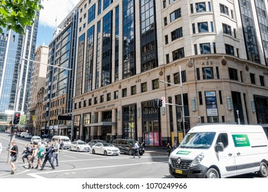 Sydney, Australia - Nov 14, 2017: The iconic Australian Stock Exchange (ASX) building, flanked by Bridge and Pitt Streets. People crossing road against vehicle traffic. Street level view.