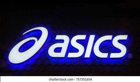 Sydney, Australia - November 03, 2017: Asics logo blue neon sign. Asics is a Japanese multinational company which produces footwear and sports equipment.