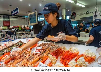 SYDNEY, AUSTRALIA - NOVEMBER 11, 2014: Vendor preparing seafood for a buyer in Famous Sydney Fish Market, Sydney, New South Wales, Australia.