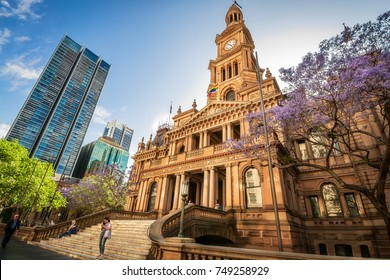 SYDNEY, AUSTRALIA - November 2, 2017: The entry to the beautiful sandstone building of Sydney Town Hall, in Victorian architectural style  in spring, with the purple jacaranda tree in the foreground.