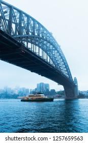 Sydney, Australia - November 5, 2018: Ferry passing through Sydney Harbour Bridge in a cold foggy morning.