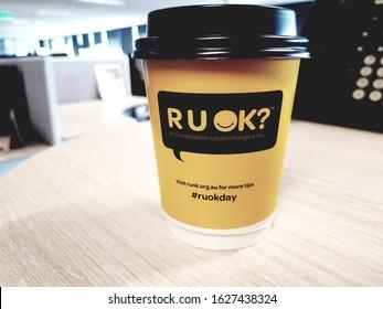 Sydney,  Australia,  NSW - 2019; An R U OK coffee cup placed  on an office desk