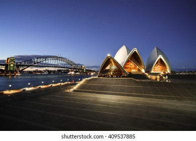SYDNEY, AUSTRALIA - OCTOBER 10, 2010: Night view of the Sydney Opera House and Harbor Bridge from behind the fence of the Tarpeian Way (Sydney, Australia)