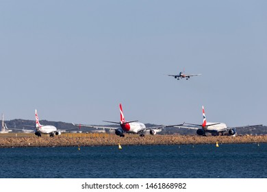 Sydney, Australia - October 10, 2013: Jetstar Airbus A320 on approach to land at Sydney Airport with a Virgin Boeing 737, Qantas Airbus A330 and British Airways Boeing 777 holding on the tarmac.