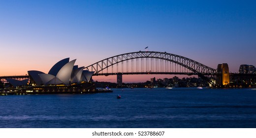 SYDNEY, AUSTRALIA - OCTOBER 14, 2016: Two of Sydney's famous icons, the Sydney Opera House and Sydney Harbour Bridge lit up at dusk after a vivid sunset, the sky still aglow with colour.