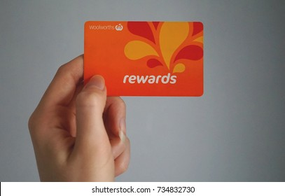 Sydney, Australia - October 15, 2017: Female caucasian hand is holding a Woolworths Rewards loyalty card, this loyalty program gives money off shopping at Woolworths Supermarkets.