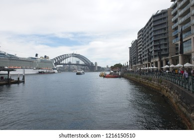 Sydney, Australia - October 20, 2018: Scenic panoramic view from Circular Quay with Sydney Harbour Bridge and cruise ship in the background and people walking along the foreshore.