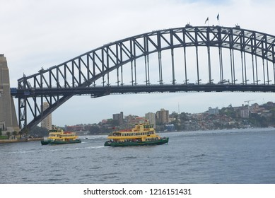 Sydney, Australia - October 20, 2018: Close up view of Sydney Harbour Bridge with ferries crossing the water and residential building along the northern shore of the harbour.
