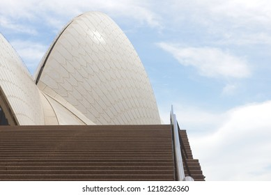 Sydney, Australia - October 20, 2018: Close up of sail of Sydney Opera House with empty stairs and handrail, blue sky and clouds as background.