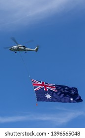 Sydney, Australia - October 5, 2013: Royal Australian Navy (RAN) Sikorsky S-70B-2 Seahawk Helicopter N24-005 towing a large Australian flag over Sydney Harbour.