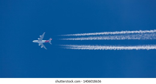 Sydney, Australia - October 5, 2013: Qantas Airbus A380 Airliner flying at high altitude with large contrails trailing across the blue sky.